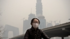 A woman wearing a protective pollution mask rides a bicycle in Beijing, China, on March 20, 2017. Nicolas Asfouri—AFP/Getty Images